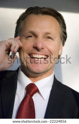 A handsome forties businessman enjoys a lighthearted conversation on his cellphone - stock photo