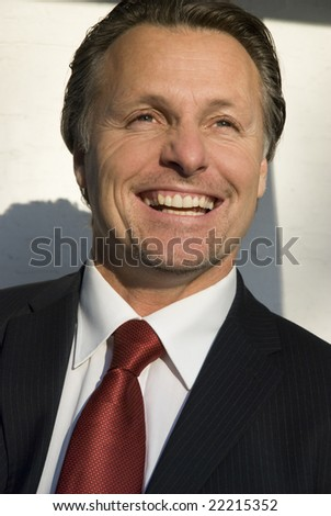 A handsome forties businessman in a smart suit shows a fantastic smile - stock photo