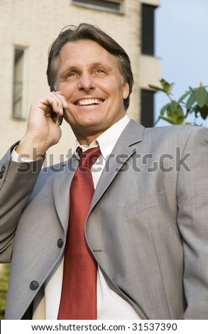 A handsome forties businessman is smiling as talks on his cellphone. - stock photo