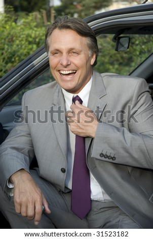 A handsome forties businessman sitting in his car and laughing. - stock photo