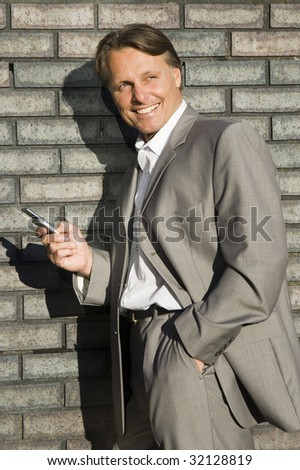 A handsome forties businessman smiling with cellphone. - stock photo