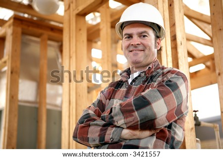 A handsome, friendly construction worker on the job site.  Authentic construction worker on actual construction site. - stock photo