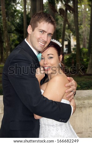 A handsome groom with his beautiful bride outdoors. - stock photo