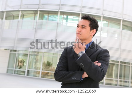 A handsome hispanic business man in front of office building - stock photo