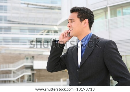A handsome hispanic business man on the phone in front of office building - stock photo