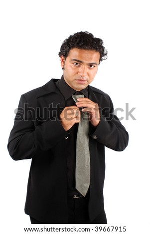 A handsome Indian businessman getting ready wearing a necktie for his office, on white studio background. - stock photo