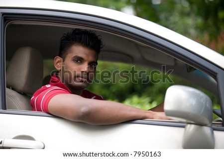 A handsome Indian man in a saloon car outside in countryside