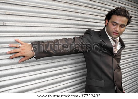 A handsome Indian model posing as a stylish businessman. - stock photo