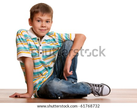 A handsome kid is smiling sitting on the wooden background; isolated on white