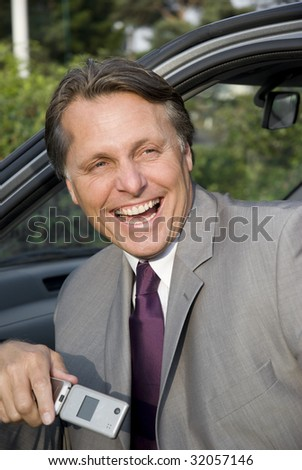 A handsome laughing businessman sitting in his car holding cellphone. - stock photo