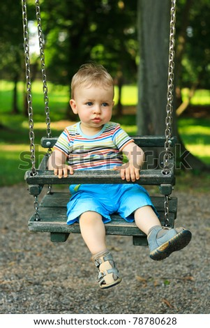 A handsome little boy swinging at the playground in the park - stock photo