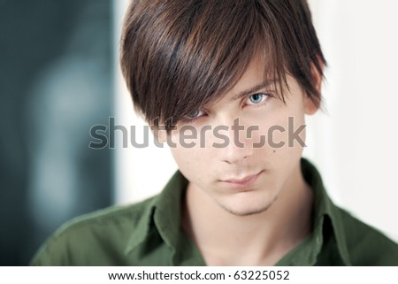 A handsome male blond teenager with blue eyes and fashionable haircut staring at the camera. Shallow depth of field on the eyes.