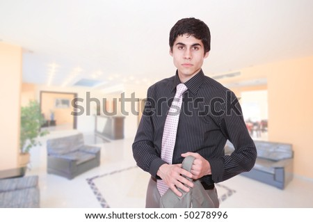 A handsome male hotel manager in the lobby