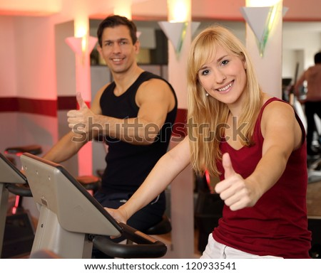 A handsome man and an attractive woman working out on a bicycle in a fitness center - stock photo