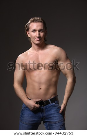 a handsome man athletic, male model posing in the studio, showing the positive and the beauty of the figure - stock photo