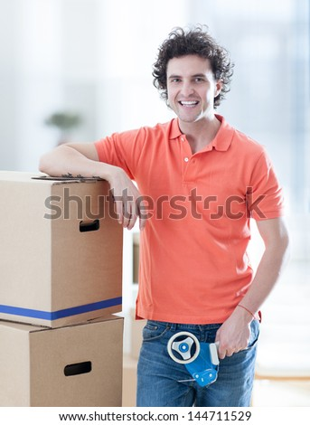 A handsome man holding a carboard box in his hands. - stock photo