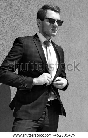 A handsome man in a suit and tie and dark glasses, monochrome