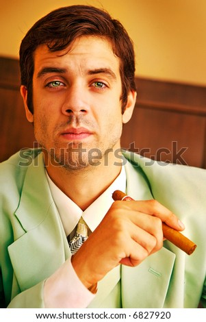 A handsome man in a suit holding a cigar.