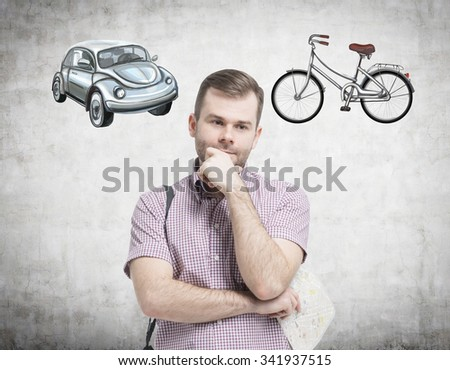 A handsome man in casual shirt is trying to chose the most suitable way for travelling or commuting. Two sketches of a car and a bicycle are drawn on the concrete wall. - stock photo