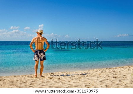 A handsome man in swimming trunks standing on exotic caribbean beach and looking out to sea, Cuba, the Caribbean, Central America - stock photo