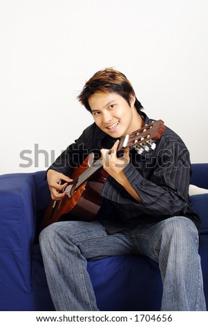 A handsome man playing a guitar