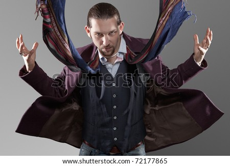 A handsome man standing in front of the camera hit by a strong wind with coat and scarf floating in the air. - stock photo