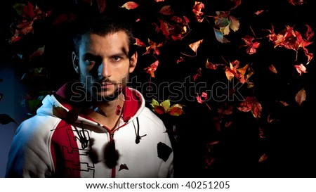A handsome man under a waterfall of falling red leaves on a black background - stock photo