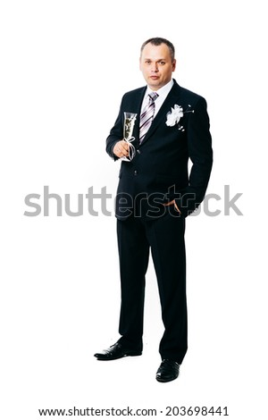A handsome man wearing a tuxedo and drinking a glass of champagne. A man wearing a black tuxedo and bow tie raising a glass of champagne, isolated on a white background.