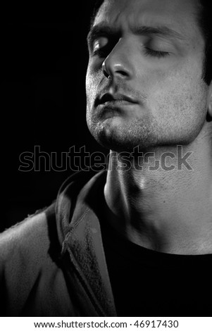 A handsome man with eyes closed, getting concentrated thinking - stock photo