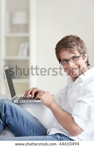 A handsome man with laptop at home - stock photo