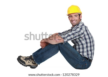 A handsome manual worker seated. - stock photo