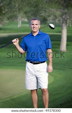 A handsome mature male golfer in his 40s-50s on the golf course - stock photo