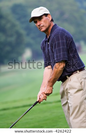 A handsome mature man on the golf course - concentrating on his game. - stock photo