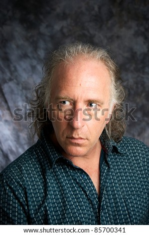 A handsome mature white american male in studio looking to the side. - stock photo