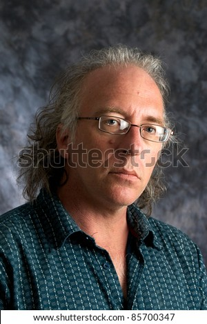 A handsome mature white american male wearing eyeglasses looking at viewer. - stock photo