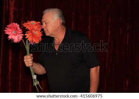 A handsome middle aged man smells fake flowers while posing in a photo booth as he has his picture taken. - stock photo