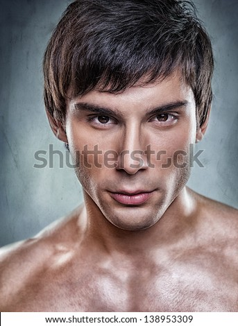 A handsome model posing in front of a gray background. - stock photo