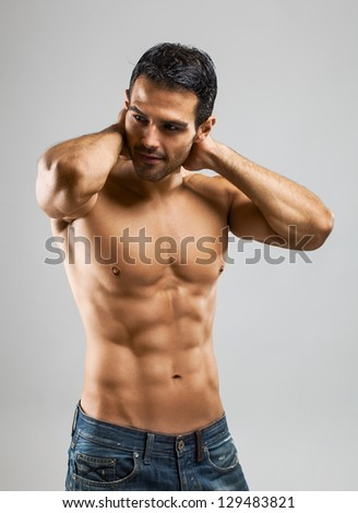 A handsome muscular man posing at a studio. - stock photo
