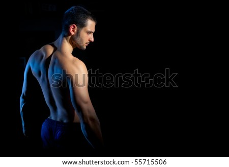 A handsome muscular man posing on a black background. Shallow depth of field with focus on model's face. - stock photo