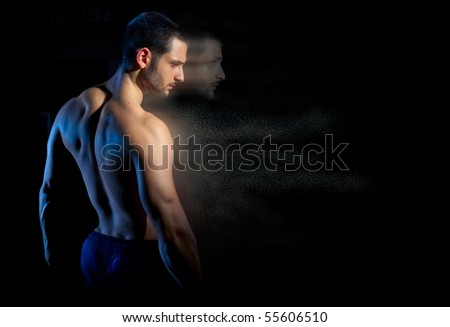 A handsome muscular man posing on a black background with his soul forging ahead in particles. Shallow depth of field with focus on model's faces. - stock photo