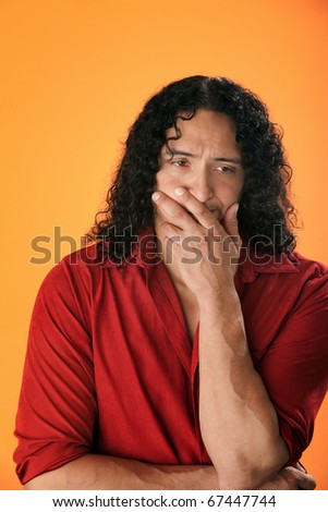 A handsome, muscular Native American man with curly hair and a red shirt looking sad or depressed - stock photo