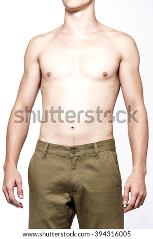 A Handsome naked muscular male model(man, boy) stand up wearing brown cotton denim pants(trousers, jeans), straight style close up isolated white at the studio. - stock photo