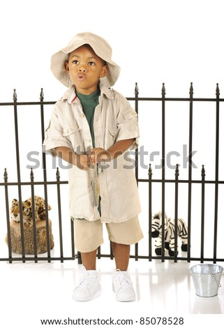 A handsome preschool zookeeper whistling as he contemplates feeding his pretend animals with the fish he's holding.  On a white background. - stock photo