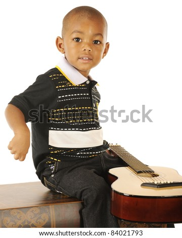 A handsome preschooler happily playing guitar on a white background. - stock photo