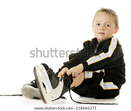 A handsome preschooler in his hockey uniform putting on his skates.  On a white background.  On a white background. - stock photo