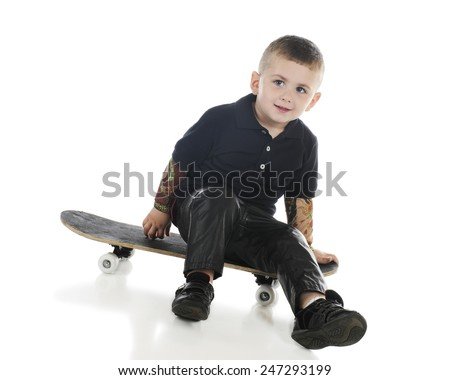 A handsome preschooler with tattooed arms and black leather pants happily sitting on a skateboard.  On a white background. - stock photo
