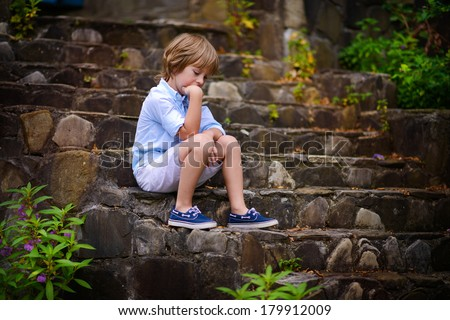 A handsome sad little boy sitting on the stone step of the old stairs and thinking about something  - stock photo