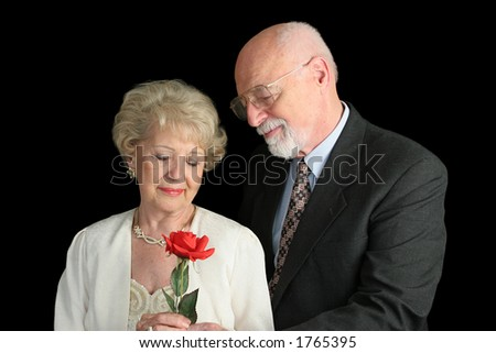 A handsome senior couple (parents of the bride) dressed up for a special occasion.  He has given her a red rose. - stock photo