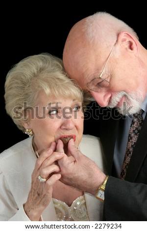 A handsome senior man romantically feeding chocolates to his beautiful wife.  Black background. - stock photo