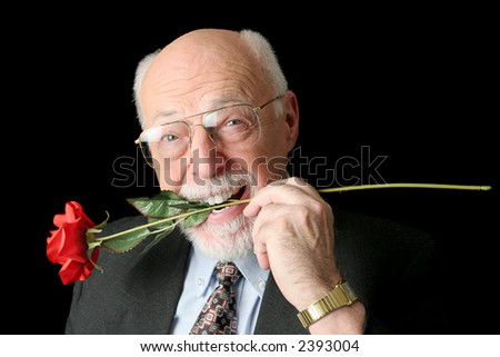 A handsome senior man with a red rose in his teeth.  Isolated on black. - stock photo